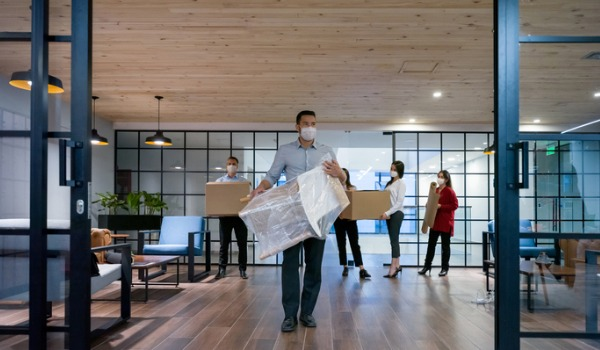 business-people-moving-into-a-new-office-wearing-facemasks-picture-id1280055643