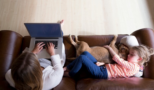 woman-using-laptop-while-daughter-and-dog-sleep-picture-id489698078